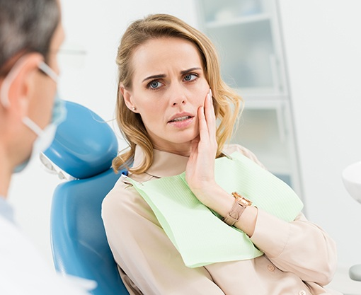Woman in dental chair holding cheek