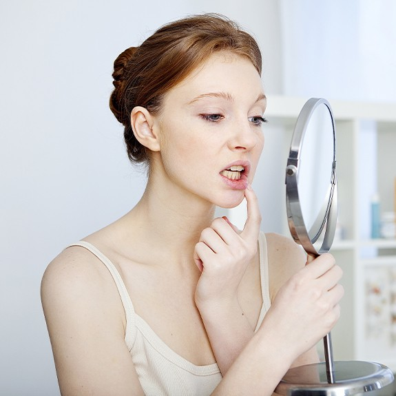 Woman looking at gums in mirror