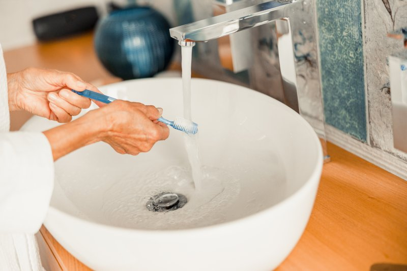 Woman sanitizing her toothbrush